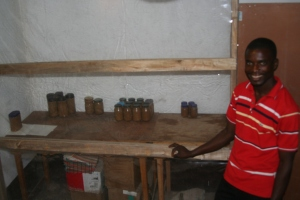 Libone manages sales and distribution of the peanut butter, which is shown in various containers to his right.  The transparent wall affords a quick visual inventory.  The peanut butter you see here is what remains of the fourth round of production.  When they make more, those rows will extend to cover the table.
